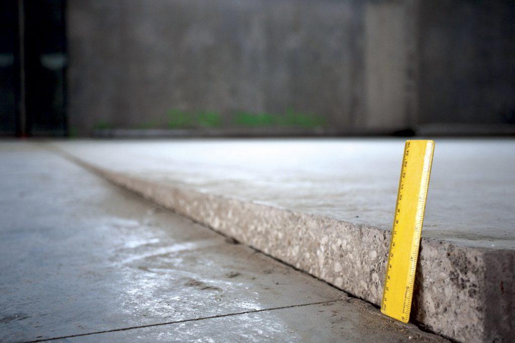 ruler leaning on a unlevelled concrete slab